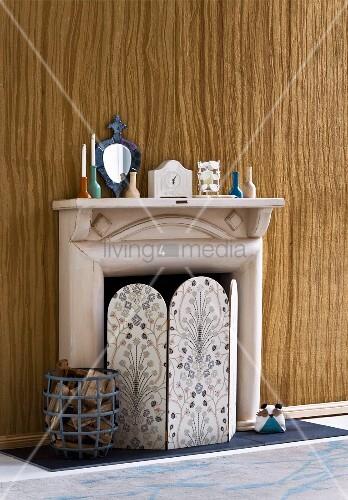 paravent mit blumenmuster im retrostil und holzscheiten im korb vor kamin aus pappmache vor wand. Black Bedroom Furniture Sets. Home Design Ideas