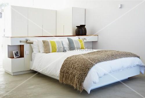 modernes doppelbett mit tagesdecke vor raumteiler in schlafbereich bild kaufen living4media. Black Bedroom Furniture Sets. Home Design Ideas