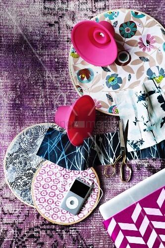 verschieden gemusterte stoffe in stickrahmen und ipod mit pinkfarbenen silikon lautsprechern auf. Black Bedroom Furniture Sets. Home Design Ideas