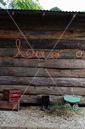 schrift love aus lichtschlauch an der aussenwand einer rustikalen holzh tte bild kaufen. Black Bedroom Furniture Sets. Home Design Ideas
