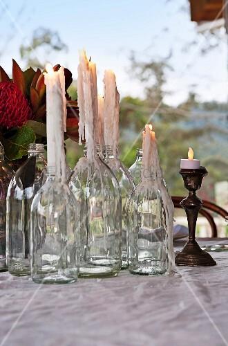 brennende tropfkerzen in leeren flaschen und silberner. Black Bedroom Furniture Sets. Home Design Ideas