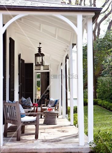 terrassenm bel aus holz auf sonniger veranda mit zugang zum garten bild kaufen living4media. Black Bedroom Furniture Sets. Home Design Ideas