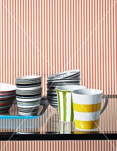 buntes geschirr auf glastisch vor rot weiss gestreifter wand bild kaufen living4media. Black Bedroom Furniture Sets. Home Design Ideas
