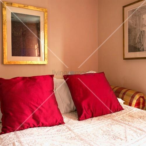 doppelbett mit roten kissen und tagesdecke ausschnitt bild kaufen living4media. Black Bedroom Furniture Sets. Home Design Ideas