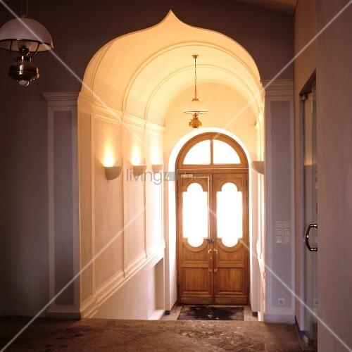 elegantes treppenhaus mit orientalischem rundbogen und blick auf holz eingangst r bild kaufen. Black Bedroom Furniture Sets. Home Design Ideas