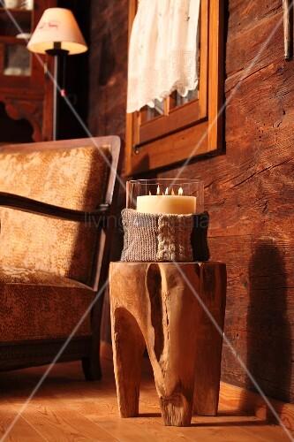 kerzenglas mit strick h lle auf baumstammhocker vor. Black Bedroom Furniture Sets. Home Design Ideas