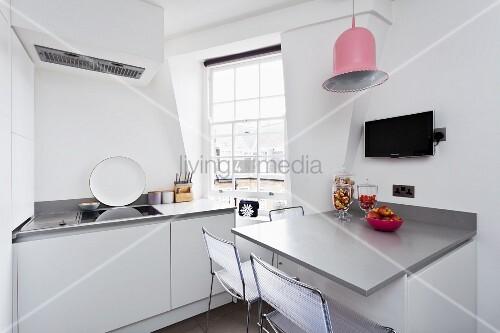 Moderne, weisse Küche mit grauem Wandtisch und einer ...