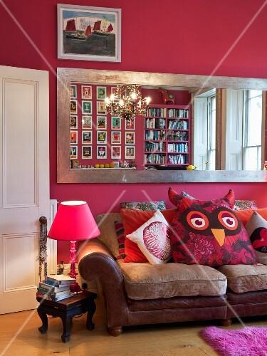 gro er wandspiegel mit silberrahmen an pinkfarbener wand ber ledercouch mit gro em eulen kissen. Black Bedroom Furniture Sets. Home Design Ideas