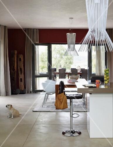 teilweise sichtbare theke mit barhocker vor essplatz und weissen schalenst hlen designer. Black Bedroom Furniture Sets. Home Design Ideas