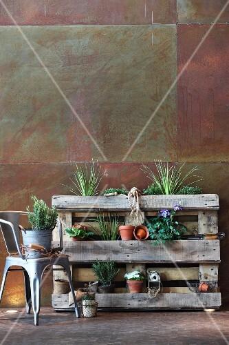 pflanzregal aus holzpalette an cortenstahl wand und metallstuhl bild kaufen living4media. Black Bedroom Furniture Sets. Home Design Ideas