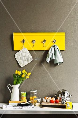 selbst gebastelte gelbe hakenleiste mit gebogenen l ffeln an der k chenwand bild kaufen. Black Bedroom Furniture Sets. Home Design Ideas
