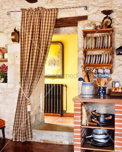 rustikale k che in mediterranem haus blick durch offenen durchgang mit gerafftem vorhang in. Black Bedroom Furniture Sets. Home Design Ideas