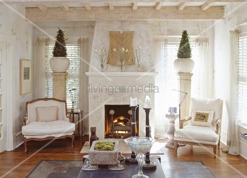 zwei antike sessel und pflanzt pfe auf dekos ulen beidseits eines wohnzimmerkamins bild kaufen. Black Bedroom Furniture Sets. Home Design Ideas