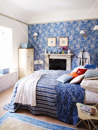Ländliches Schlafzimmer in Weiss und Blau mit Doppelbett vor Kamin – Bild kaufen – living4media