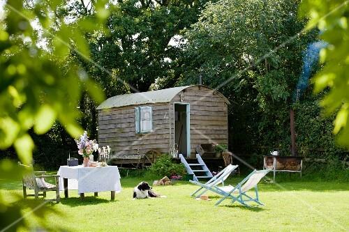 nostalgischer wohnwagen auf gr ner wiese mit gedecktem tisch und hellblauen liegest hlen in. Black Bedroom Furniture Sets. Home Design Ideas