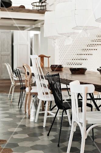 esstisch mit verschiedenen st hlen auf fliesenboden und h ngeleuchten mit weissen stoffschirmen. Black Bedroom Furniture Sets. Home Design Ideas