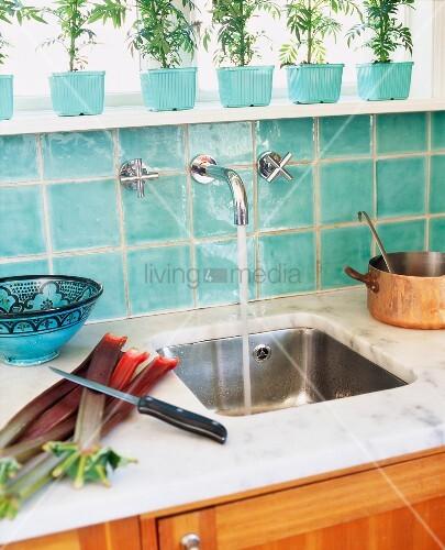 sp lbecken vor t rkisen wandfliesen unter fensterbank mit aufgereihten blument pfen bild. Black Bedroom Furniture Sets. Home Design Ideas