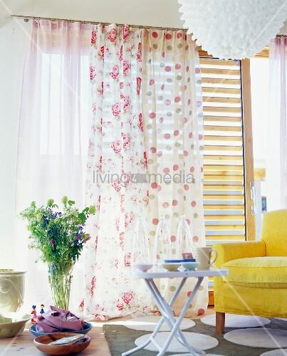 sommerstrauss vor duftigen gardinen mit punkten und rosen zu gelbem polstersessel bild kaufen. Black Bedroom Furniture Sets. Home Design Ideas