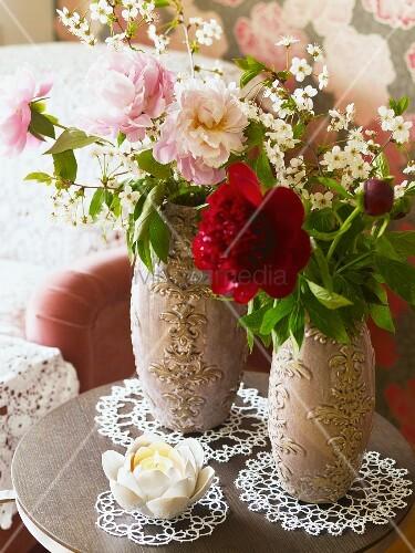 pfingstrosen in zwei verzierten vasen und bl tenkerze auf spitzendeckchen bild kaufen. Black Bedroom Furniture Sets. Home Design Ideas