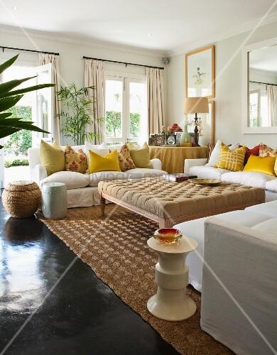 gro er gepolsterter tisch inmitten wei er polstersofas mit vielen gelben kissen in hellem. Black Bedroom Furniture Sets. Home Design Ideas