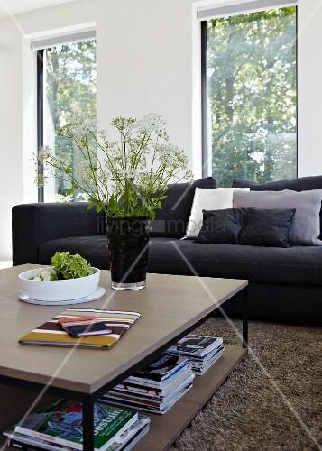 quadratischer couchtisch vor schwarzer couch in wohnzimmer mit gro en fenstern auf dem tisch. Black Bedroom Furniture Sets. Home Design Ideas