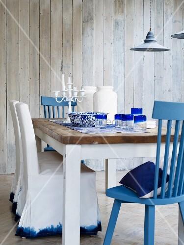 Esszimmer in blau weiss mit holztisch & verschiedenen stühlen ...