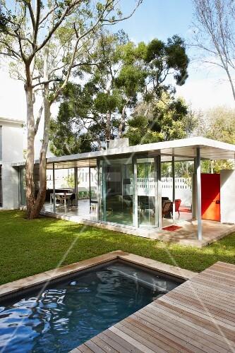blick von pool mit holzterrasse auf den wohnbereich hinter der verglasten fassade bild kaufen. Black Bedroom Furniture Sets. Home Design Ideas