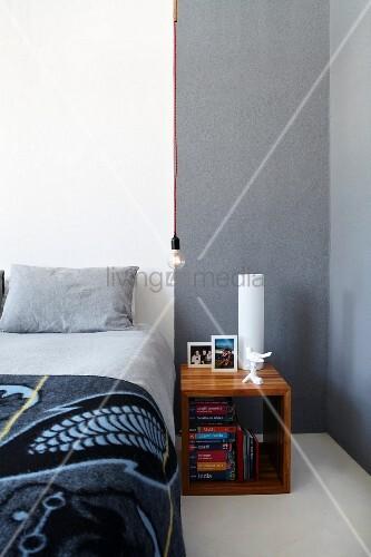 quadratisches nachtk stchen aus edelholz neben bett mit. Black Bedroom Furniture Sets. Home Design Ideas