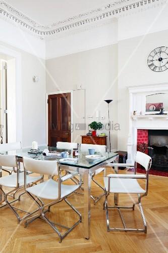 esstisch mit glasplatte und weisse lederst hle im hintergrund offener kamin in herrschaftlichem. Black Bedroom Furniture Sets. Home Design Ideas