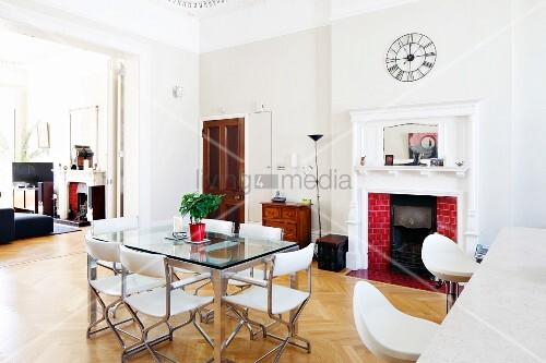 esstisch mit glasplatte und weisse lederst hle vor offenem kamin in herrschaftlichem ambiente. Black Bedroom Furniture Sets. Home Design Ideas