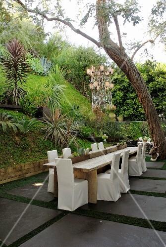 st hle mit weisser husse um holztisch auf terrassen platz in tropischem garten bild kaufen. Black Bedroom Furniture Sets. Home Design Ideas
