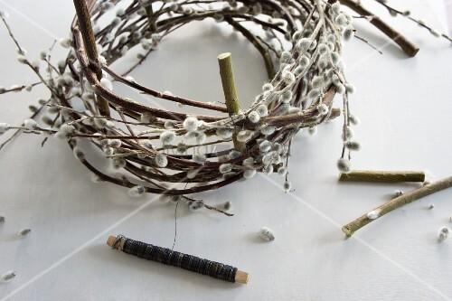 kranz aus weidenk tzchen wird geformt bild kaufen living4media. Black Bedroom Furniture Sets. Home Design Ideas