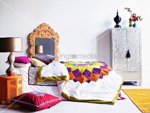 bett mit gesteppter tagesdecke und mehreren kissen dekoriert kunsthandwerklicher spiegelrahmen. Black Bedroom Furniture Sets. Home Design Ideas