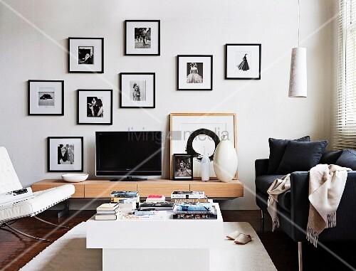designer tv m bel mit schwarzem bildschirm umgeben mit verschiedenen schwarz wei aufnahmen in. Black Bedroom Furniture Sets. Home Design Ideas