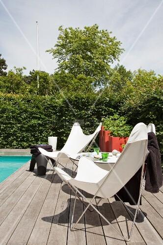 butterfly st hle mit weissem spannbezug auf holz dielenboden am poolrand bild kaufen. Black Bedroom Furniture Sets. Home Design Ideas
