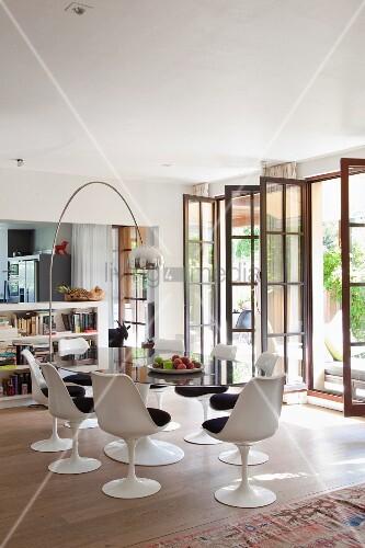 weisse tulip st hle mit dunklen sitzpolstern um ovalem glastisch unter bogenlampe an der seite. Black Bedroom Furniture Sets. Home Design Ideas