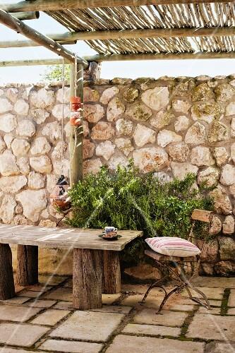 vintage gartenstuhl mit kissen und rustikale holzbank auf steinboden einer terrasse mit bambus. Black Bedroom Furniture Sets. Home Design Ideas