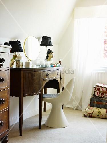 weisser schalenstuhl vor antiker schminktisch aus dunklem holz an fenster mit vorhang bild. Black Bedroom Furniture Sets. Home Design Ideas