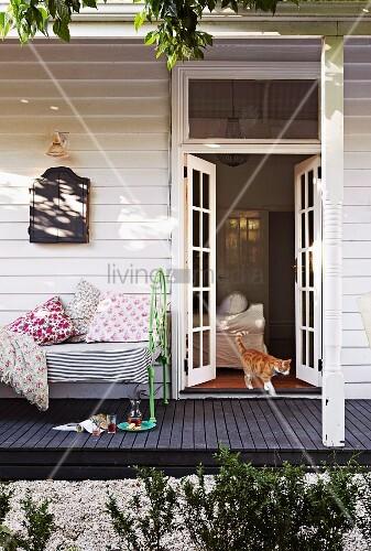weisses holzhaus mit offener terrassent r katze spaziert hinaus gem tliches vintage tagesbett. Black Bedroom Furniture Sets. Home Design Ideas