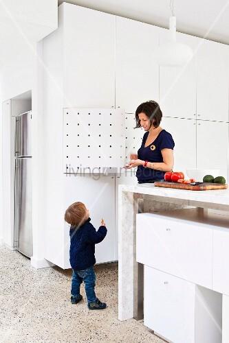 mutter mit kind in offener k che k chentheke aus stein und eingeschobenen weissen. Black Bedroom Furniture Sets. Home Design Ideas
