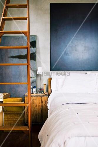 bett mit wei er betw sche und dunklem bild am kopfende lange angelehnte holzleiter und alte. Black Bedroom Furniture Sets. Home Design Ideas