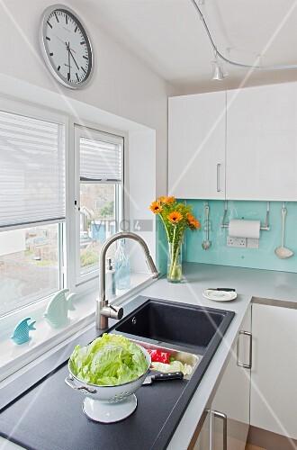 moderne weisse k chenzeile bereck salat im sieb auf sp le vor fenster mit halb geschlossenem. Black Bedroom Furniture Sets. Home Design Ideas