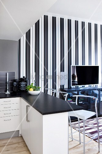 Open plan kitchen with black worksurface on breakfast bar and stools  TV sideboard against elegant white striped wallpaper in background