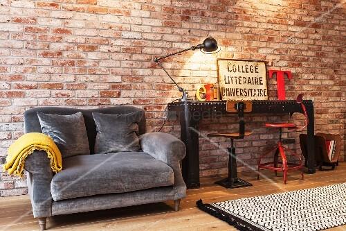 graue polstercouch neben schwarzem metalltisch und vintage drehst hlen vor beleuchteter. Black Bedroom Furniture Sets. Home Design Ideas