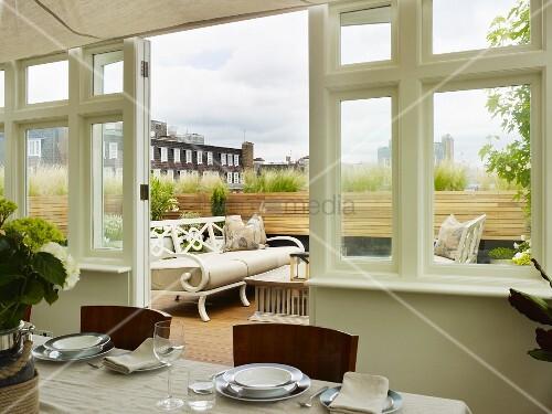 gedeckter tisch im wintergarten mit blick auf dachterrasse und weisse nostalgische sitzbank. Black Bedroom Furniture Sets. Home Design Ideas