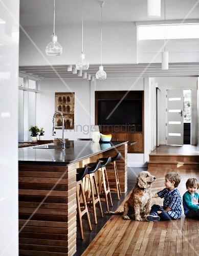 zwei kinder spielen mit hund auf dielenboden vor mittelblock unter ... - Küche Mittelblock