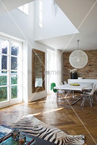 Double Height Ceiling In Open Plan Living Area With Zebra Skin Rug On Herringbone Parquet Floor