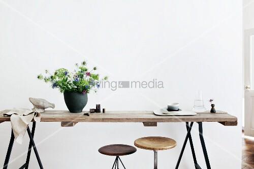 schwarze keramikvase mit blumenstrauss nigella auf rustikaler holzplatte und metall b cke. Black Bedroom Furniture Sets. Home Design Ideas
