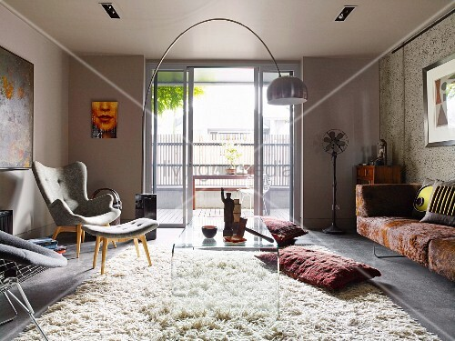 couchtisch aus transparentem kunststoff und sessel mit passendem schemel auf flokatiartigem. Black Bedroom Furniture Sets. Home Design Ideas