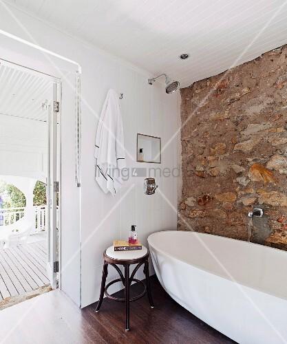 thonet hocker neben moderner freistehender badewanne vor natursteinwand und offener terrassent r. Black Bedroom Furniture Sets. Home Design Ideas